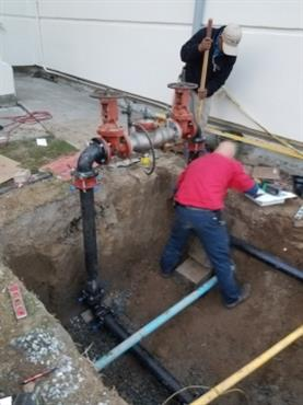 plumber in trench with pipes