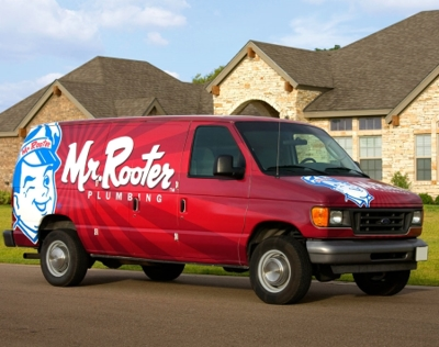 Mr. Rooter Van parked in the street outside a customer's home.