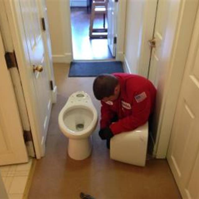 Mr. Rooter Plumber fixing a toilet