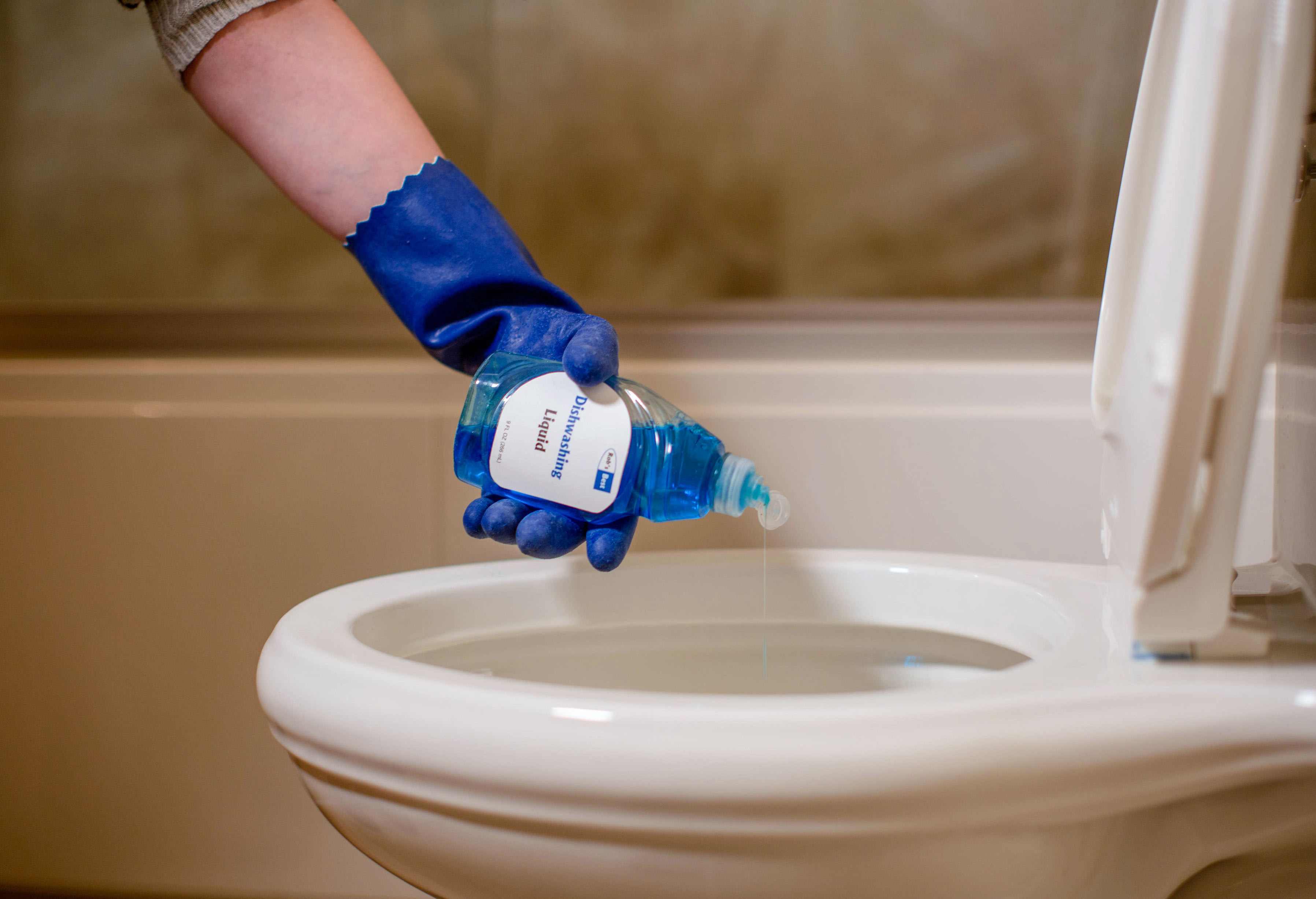 Person pouring diswashing soap in toilet