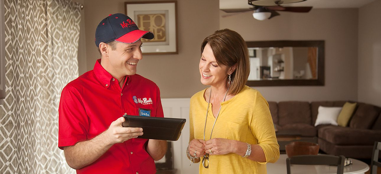 Mr. Rooter Plumber showing a tablet to a customer