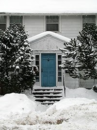 Front of white house with blue door in snowy winter