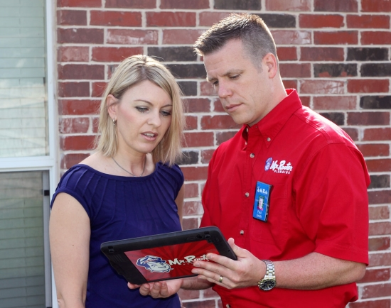 Mr. Rooter Plumber Showing Customer Tablet