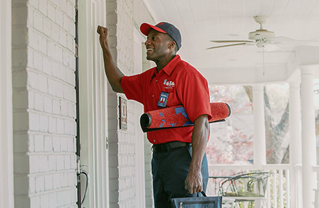 Mr. Rooter Plumber in uniform, knocking on a front door