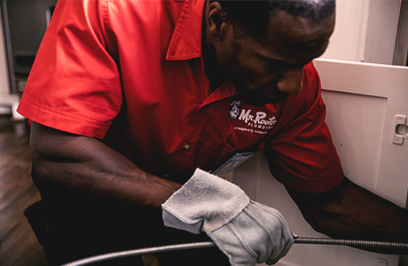 Mr. Rooter Plumber cleaning a drain