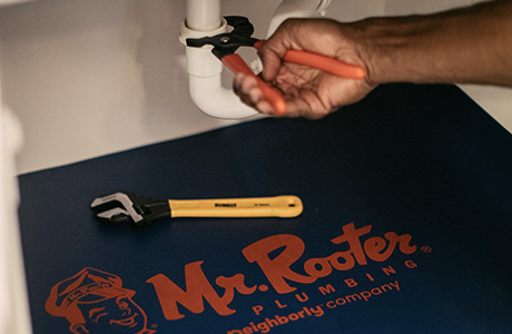 Mr. Rooter plumber fixing a pipe