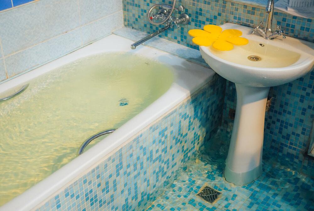 Затопленная ванна и раковина в ванной, облицованной синей плиткой