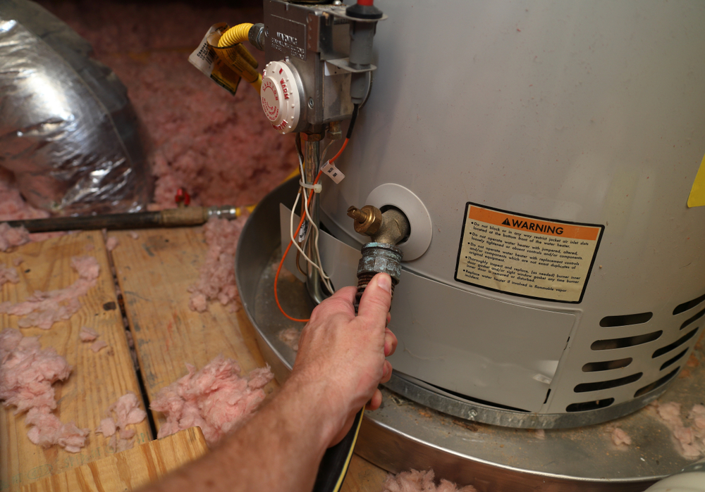 Gas Water Heater Getting Checked by Hand