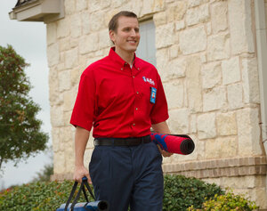 Mr. Rooter tech carrying supplies on the way to a job
