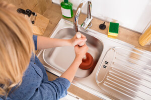 Woman plunging a kitchen drain
