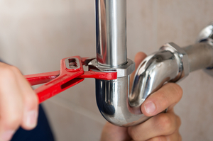 Hands fixing a pipe with a red wrench