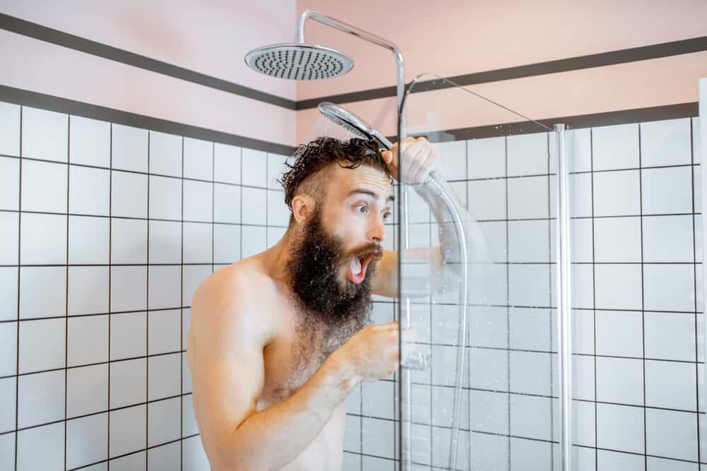 Bearded man in shockingly cold shower