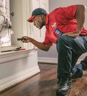 Mr. Rooter plumber inspecting a water heater